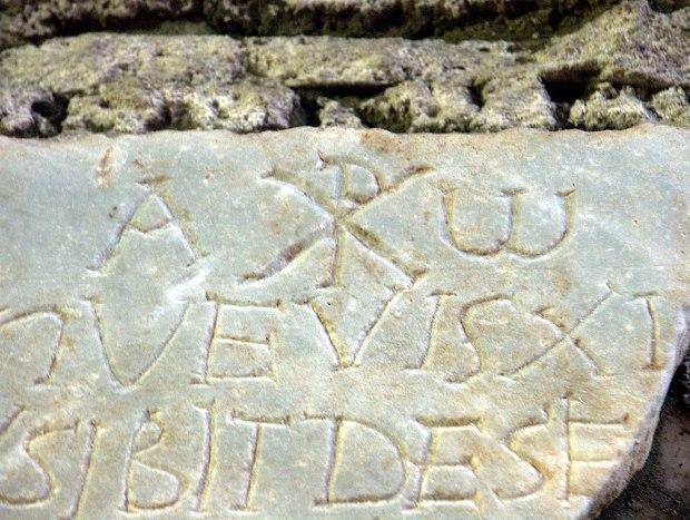 1024px-Rom,_Domitilla-Katakomben,_Steintafel_mit_Inschrift,_Alpha_und_Omega_und_Christussymbol_Chi_Rho